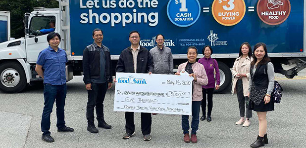 Tian-Jin Temple volunteers hold cheque showing donations to Food Bank