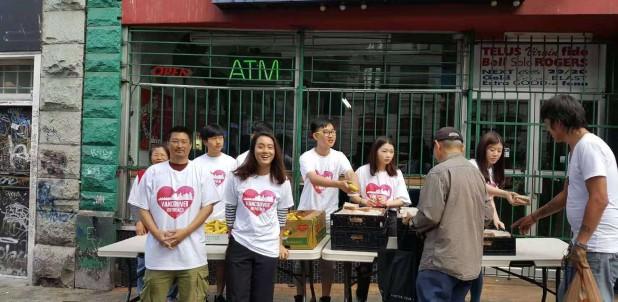 左二為王夢蝶和天金堂的義工們在溫哥華東區發放三明治和水果給街友