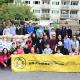 Group photo of association volunteers standing in front of Food Bank fundraiser bins